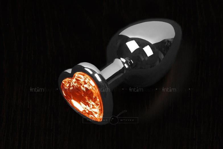 Большая анальная пробка Пикантные Штучки с оранжевым кристаллом в виде сердечка, серебристая, 8.5 см